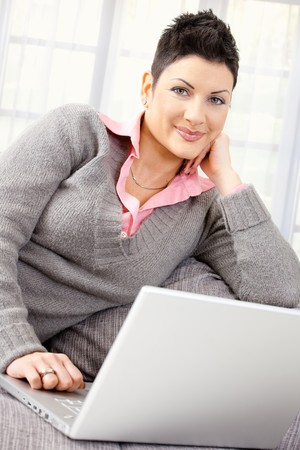 teleworking: Young woman sitting on couch teleworking on laptop computer at home. Stock Photo