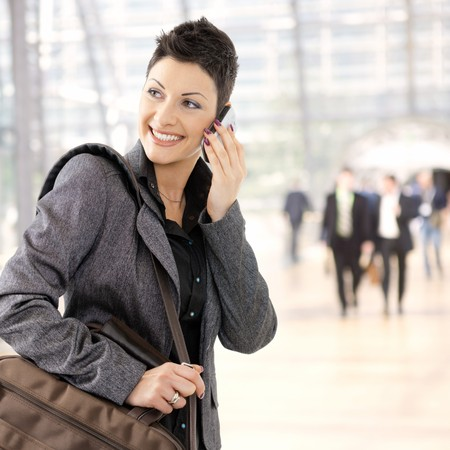 one young adult woman: Portrait of happy young businesswoman calling on mobile phone, smiling.