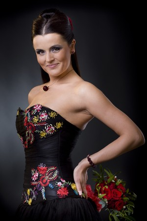 Beautiful young woman posing in a black cocktail dress holding a bouqet of red roses, looking flirtatious. photo