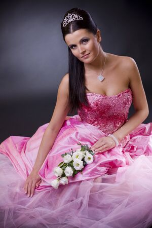 bouqet: Smiling young bride sitting in a pink wedding dress, holding bouqet of white flowers.