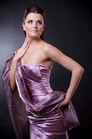 robo: Joven y bella mujer posando, vestido con una luz violeta vestido de noche con robaron. Foto de archivo