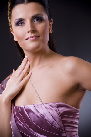 Closeup portrait of a beautiful young woman wearing a light purple evening dress. photo