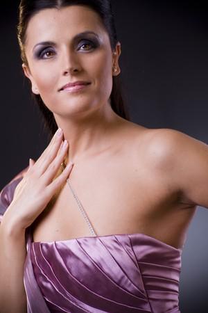 Closeup portrait of a beautiful young woman wearing a light purple evening dress. photo