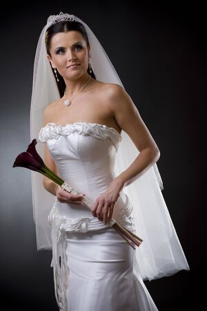 Studio portrait of a young bride wearing a white wedding dress with veil, holding flowers. photo