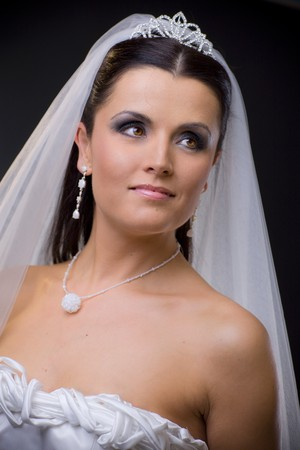 Closeup portrait of a young bride wearing white wedding veil, smiling. photo