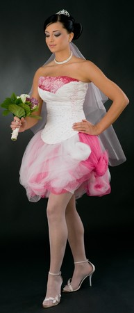 Beautiful young bride in tied up, white and pink wedding dress and white stockings, holding bouquet of flowers. photo