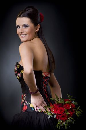 Beautiful young woman posing in a black cocktail dress holding a bouqet of red roses, looking back flirtatious. photo
