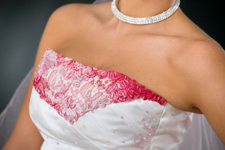 Closeup photo of wedding dress, with pink embroidery and beads. photo