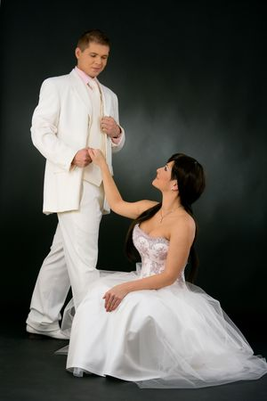 black and white photography: Portrait of wedding couple. Bride wearing romantic white wedding dress, sitting on floor and looking up to groom in white suit. They are holding hands. Stock Photo