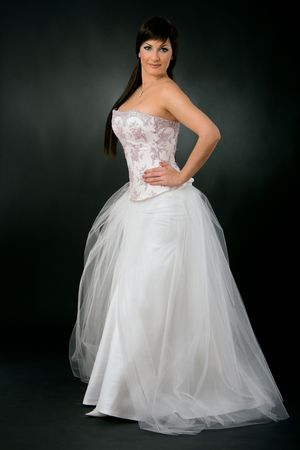 Bride wearing romantic white wedding dress, posing with her hands on hip, looking at camera, smiling. photo