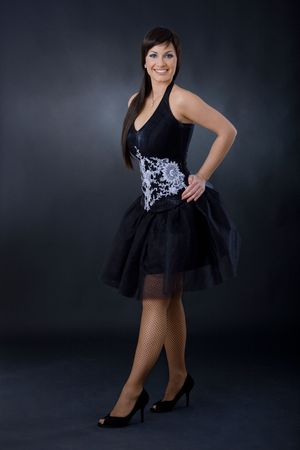 Beautiful young woman is black cocktail dress, posing with hands on hips. photo