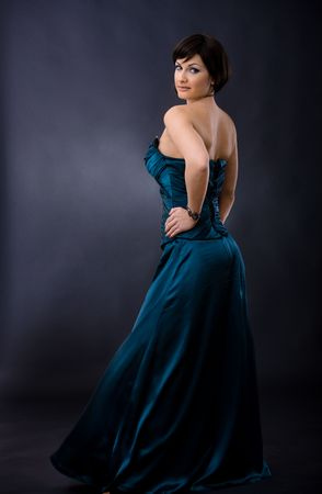 Studio portrait of beautiful young woman wearing dark blue evening dress, posing with hands on hip, smiling, looking back. photo