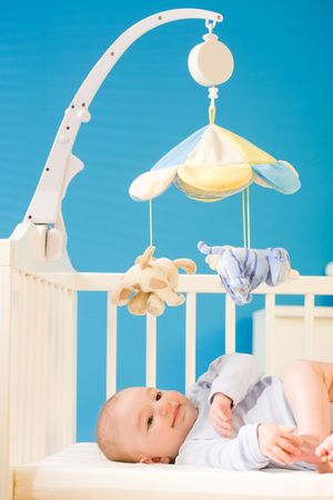 Infant baby resting and playing in his little baby bed at nursery. Toys are officially property released. Stock Photo - 4583344
