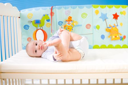 soft toy: Cute baby boy (4 months old) lying on back in baby bed.