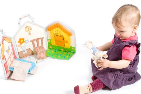 Baby girls sitting on floor playing with stuffed story book. Isolated on white. Toys are officially property released. photo
