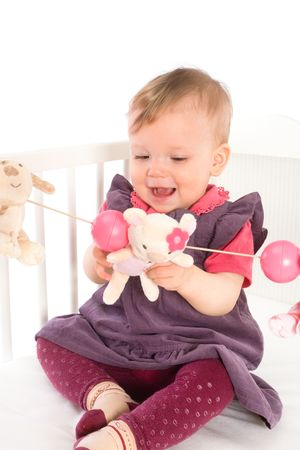 Cute baby girl (1 year old) sitting on crib, holding soft toys. Isolated on white, smiling. Toys are offically property released. Stock Photo - 4583365