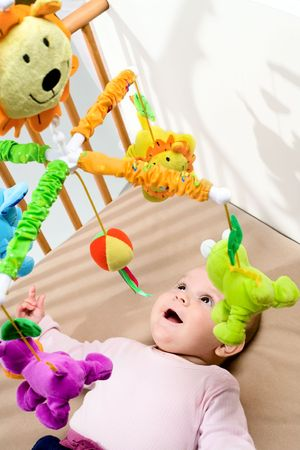 Happy baby playing with bed side toy, smiling. photo