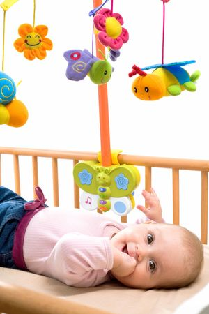 Happy baby playing with bed side toy, smiling, isolated on white background. Stock Photo - 4583337