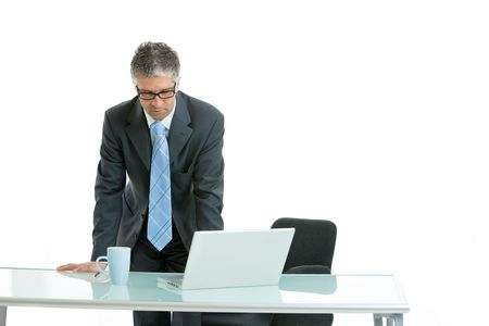 Worried businessman leaning on office desk with laptop computer on it, looking down. Isolated on white. Stock Photo - 4608073