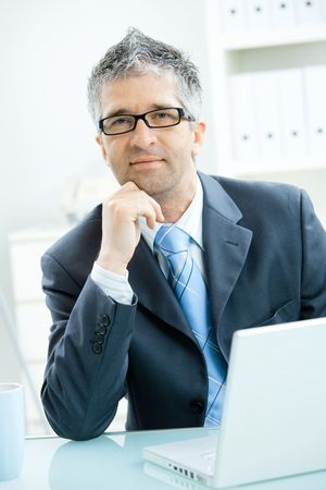 Businessman with grey hair, wearing grey suit and glasses thinking over laptop computer, sitting at office desk leaning on hand. photo