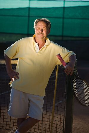 70s tennis: Portrait of an active senior man in his 70s on the tennis court.