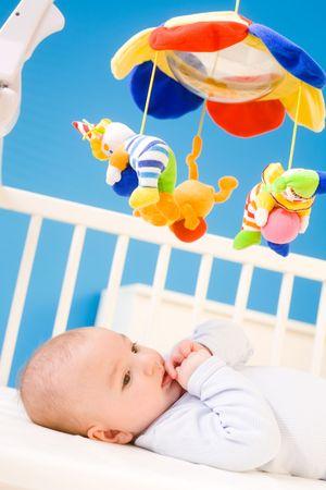 Bébé de quatre mois de repos sur le CRIG crèche et à exercer avec son pouce. Les jouets sont officiellement la propriété libérée.