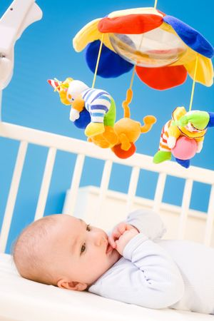 Four months old baby resting on crig at nursery and plying with his little thumb. Toys are officially property released. Stock Photo - 4608040