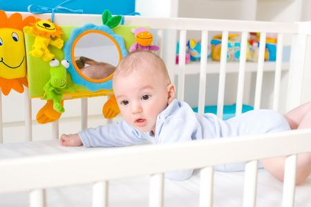 soft toy: Infant baby lying in baby bed at childrens room. Toys are officially property released. Stock Photo