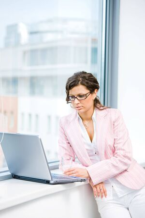 Young attractive businesswoman browsing internet on laptop computer in fron front of office window. Stock Photo - 4608060