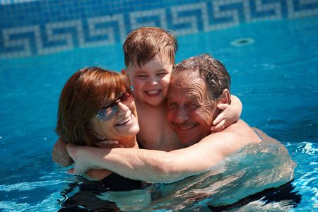 Happy family: grandparents having bath in pool together with grandson (3 years), smiling, outdoor, summer. photo