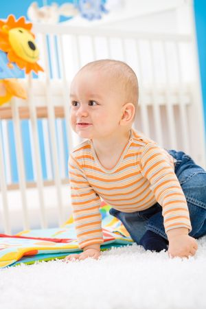 Baby boy ( 1 year old ) sitting on floor at home and playing. Toys are property released. photo