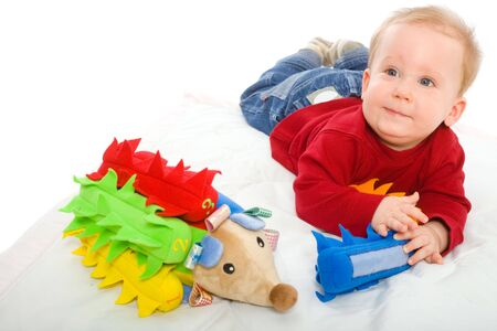 Happy baby boy (6 months old) playing with soft toys, smiling. Toys are property released. photo