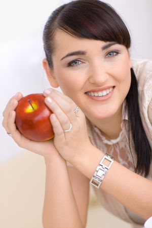Closeup portrait of happy young woman holding red apple in hands, smiling. photo