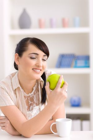 Portrait of a beautiful young woman sitting at table holding green apple in hand, smiling. photo