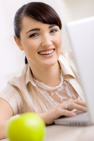 Closeup portrait of happy young women browsing internet on laptop computer at home, smiling. photo