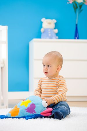 1 year old: Baby boy ( 1 year old ) sitting on floor at home and playing. Toys are property released.