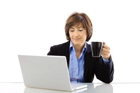 Senior businesswoman using laptop computer while drinking coffee, looking at screen and smiling. Isolated on white background. photo