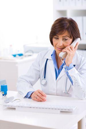Senior female doctor calling on phone, smiling. Stock Photo - 4720111