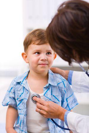 Senior female doctor examining little child boy. photo