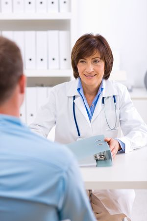 Smiling senior female doctor talking with male patient at office. photo