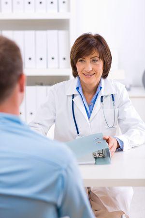 doctora: Sonriendo altos doctora hablar con el paciente de sexo masculino en la oficina.