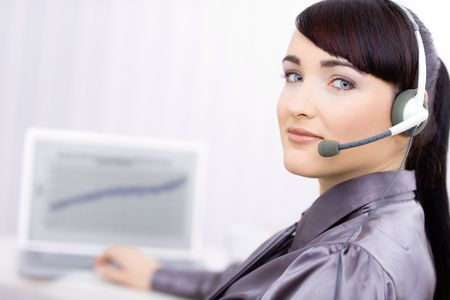 Happy young female customer service operator talking on headset, sitting in front of computer screen, smiling. photo