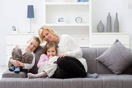 bambini seduti: Madre e bambino seduto sul divano insieme al soggiorno. Archivio Fotografico
