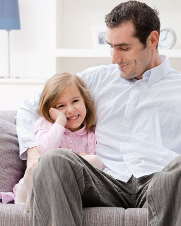 blond brown: Little girl wearing pink dress sitting on couch embraced by her father, smiling.