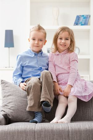 sister and brother: Portrait of happy little siblings sitting together on couch, smiling.  Stock Photo