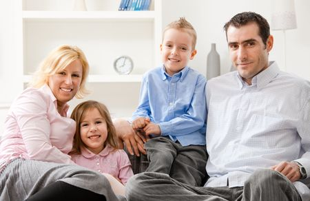Familiy portrait, parents with two children sitting together on sofa at home, smiling. photo