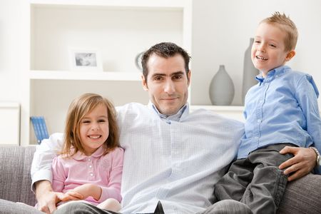 Happy family, father and children sitting together on couch, smiling. Stock Photo - 5024731