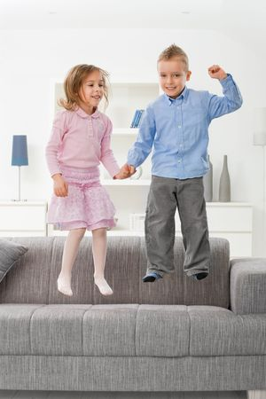 Happy children jumping on couch at home, smiling. photo