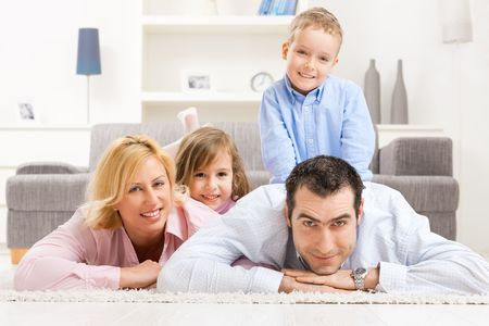 Portrait of happy family lying heaped on floor in living room, smiling. photo