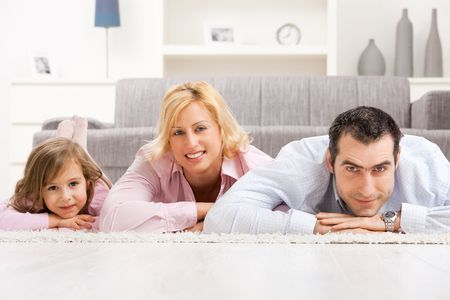 Happy couple and their daugther lying together on floor in living room. Stock Photo - 5024733